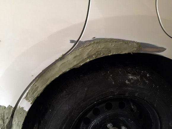 車の深くえぐれた傷に1回目のパテを塗った後